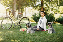 Young woman with dogs and bicycle having picnic in the park Royalty Free Stock Photos