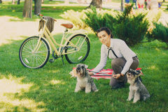 Young woman with dogs and bicycle having picnic in the park royalty free stock photography