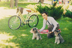 Young woman with dogs and bicycle having picnic in the park stock photo