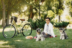 Young woman with dogs and bicycle having picnic in the park royalty free stock image