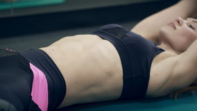 Young woman doing abdominal crunches on floor in gym indoor. stock video footage