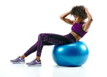 Young woman doing abs exercise on fitness ball. Photo of african girl in silhouette on white background. Fitness and healthy lifestyle concept Royalty Free Stock Photo