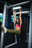 Young woman doing abs exercise. In fitness club background Royalty Free Stock Photos