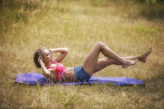 Young woman doing abs exercise. Young woman doing abs exercise outdoors Royalty Free Stock Image