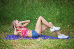 Young woman doing abs exercise outdoors. In summertime Stock Photos