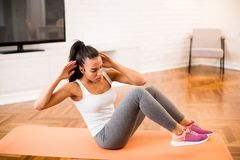 Young woman doing abs exercise in the room. Young woman doing abs morning exercise in the room Royalty Free Stock Photos