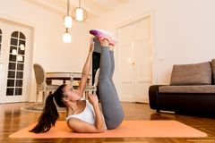 Young woman doing abs exercise in the room. Young woman doing abs morning exercise in the room Stock Image