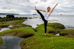 Young woman doing acrobatic exercises at the intertidal zone of stock images