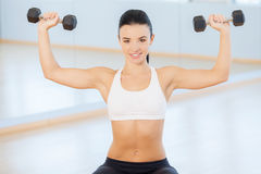 Young woman doing arm curls. Stock Photos