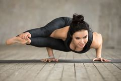 Young woman doing Astavakrasana exercise. Young sporty woman practicing yoga, doing Eight Angle exercise, Astavakrasana pose, working out, wearing sportswear Stock Photography