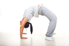 Young woman doing back bend. On floor over white background royalty free stock photography