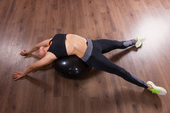 Young Woman Doing Back Bend Over Exercise Ball Stock Photo