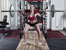 Young woman doing barbell squats Stock Images