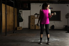 Young woman doing bicep curls. Full length view of a pretty young woman doing bicep curls with dumbbells in a dark gym Royalty Free Stock Image