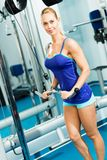 Young woman doing body-building in the Gym Royalty Free Stock Photography