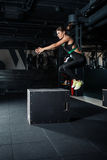 Young woman doing a box jump exercise. Muscular woman doing a box squat at the gym Stock Photo
