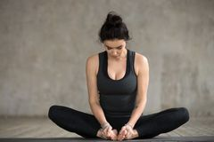 Young woman doing Butterfly exercise. Young sporty woman practicing yoga, doing Butterfly exercise, baddha konasana pose, working out, wearing sportswear, black Stock Images