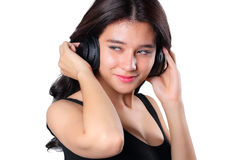 Young woman doing a bWoman listening to music on headphones enjoying a musicicep curl isolated on whit Stock Photo