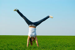 Young woman doing cartwheel Stock Images