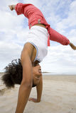 Young woman doing cartwheel on beach Royalty Free Stock Photo