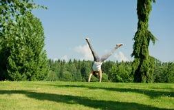Young woman doing cartwheel outside Stock Photos