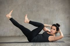 Young woman doing crisscross exercise. Young sporty woman practicing fitness, doing crisscross exercise, bicycle crunches pose, working out, wearing sportswear royalty free stock photo