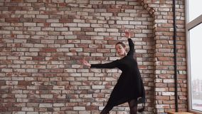 Young woman is doing dance steps, moving hands in a rehearsal hall stock video