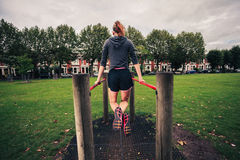 Young woman doing dips in the park Royalty Free Stock Photography