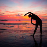 Young woman doing exercise on the beach Royalty Free Stock Photo