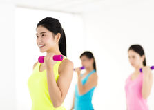 Young woman doing exercise with dumbbell in gym Stock Photo