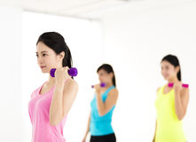Young woman doing exercise with dumbbell in gym Stock Photos