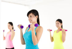 Young woman doing exercise with dumbbell in gym Royalty Free Stock Photo