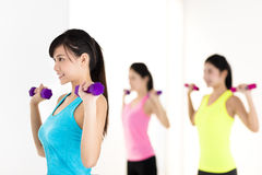 Young woman doing exercise with dumbbell in gym Royalty Free Stock Photos