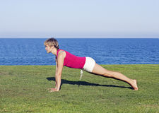 Young woman doing exercise on green grass Stock Photography