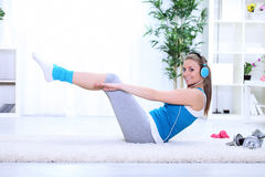 Young woman doing exercise for stomach. Young smiling girl doing exercise for stomach, full length Royalty Free Stock Photos