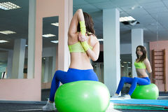 Young woman doing exercise and stretching on a fitness ball Stock Photo