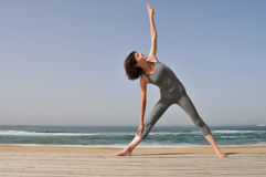 Young woman doing exercises on the beach Stock Image