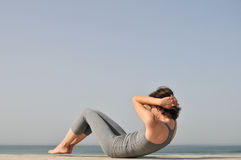 Young woman doing exercises on the beach Stock Photography