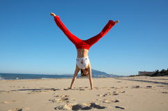 Young woman doing exercises on the beach. And the blue sky Stock Photography