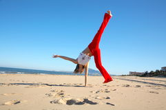 Young woman doing exercises on the beach. And the blue sky royalty free stock images