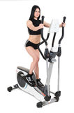 Young woman doing exercises on elliptical cross trainer Stock Photos