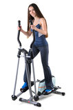 Young woman doing exercises on elliptical trainer Stock Photos