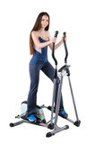 Young woman doing exercises on elliptical trainer Stock Photography