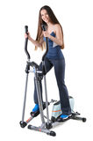 Young woman doing exercises on elliptical trainer Stock Image