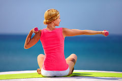Young woman doing exercises with hand weights on the beach Stock Images