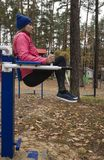Young woman, exercise on a sports similator, nature, autumn, lifestyle, forest. royalty free stock images