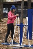Young woman, exercise on a sports similator, nature, autumn, lifestyle, forest. royalty free stock image
