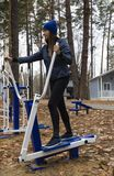 Young woman, exercise on a sports similator, nature, autumn, lifestyle, forest. stock photography