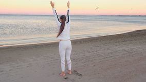 Young woman is doing exercises to restore breathing on the sand beach at sunrise in autumn. stock footage