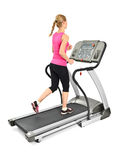 Young woman doing exercises on treadmill. On white background, some blurred motion Royalty Free Stock Photography